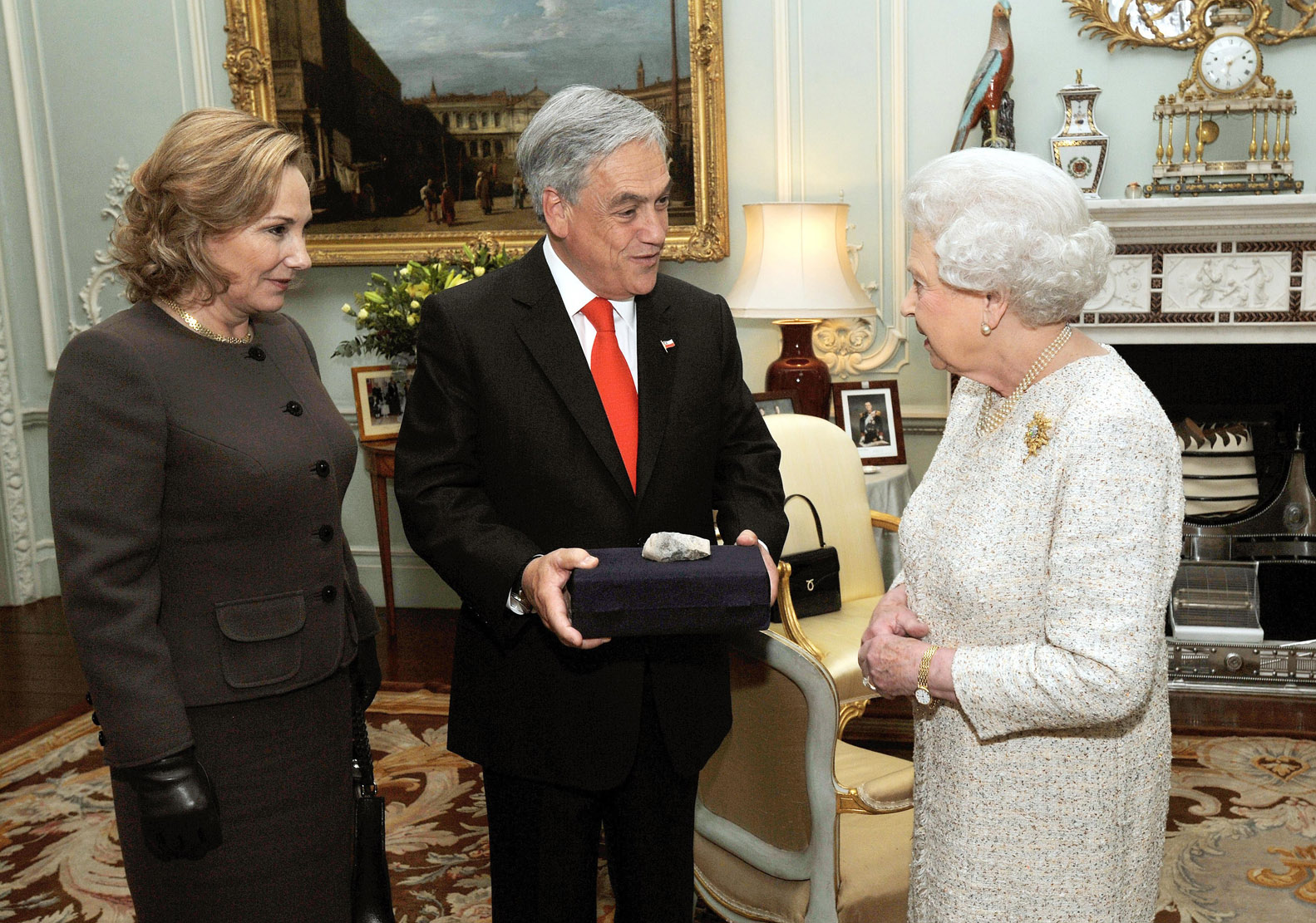 Piñera regalándole una pierdra de la Mina San José a la Reina Isabel II. Foto: Licencia Creative Commons